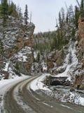 Дорога зимы между горами с лесом и снегом Стоковая Фотография