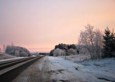 Дорога зимы на заходе солнца Стоковые Изображения