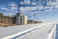 Дорога зимы на предпосылке конструкции новых домов Стоковые Изображения RF