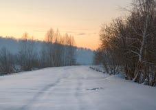 Дорога зимы окруженная деревьями на восходе солнца стоковые фотографии rf