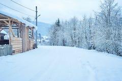 Дорога зимы после снежностей вдоль деревянной конструкции Стоковая Фотография