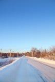 Дорога зимы снежная в маленьком городе на солнечном дне Стоковое фото RF