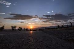 Дорога исчезая к горизонту под солнцем излучает приходить вниз ринв драматические бурные облака Заход солнца на дороге горы Azerb Стоковые Изображения