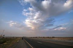 Дорога исчезая к горизонту под солнцем излучает приходить вниз ринв драматические бурные облака Заход солнца на дороге горы Azerb стоковое фото