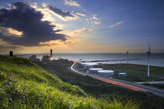 Дорога и ветрянки во время захода солнца Стоковая Фотография RF