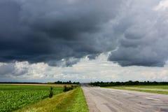Дорога и драматическое бурное небо Стоковые Изображения RF