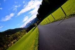 Дорога и малая деревня в горах горных вершин Стоковое Изображение RF