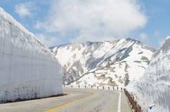 Дорога и стена снега на трассе kurobe tateyama горных вершин Японии высокогорной Стоковое Изображение RF