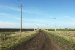 Дорога, которая идет среди полей внутри Стоковые Фото
