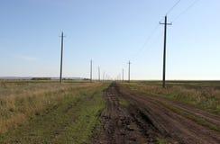 Дорога, которая идет среди полей внутри Стоковая Фотография