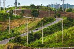 Дорога к кривой на холме с электрическими поляками стоковое фото rf