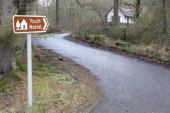 Дорога направления знака общежития молодости ведущая к bothy гостинице для туристов ходоков в сельской местности древесин леса Стоковое Фото