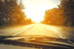 Дорога осени на заходе солнца Стоковые Изображения