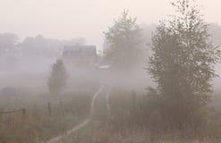 Дорога осени тайны с туманом в предпосылке утра Стоковое Изображение