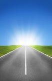 Дорога, поля и голубое небо Стоковые Изображения