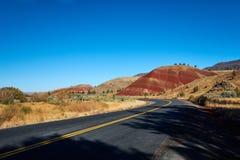 Дорога проходя покрашенный холм Стоковое Фото