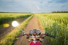 Дорога, пшеничное поле и облака ландшафта лета Езды мотоцикла Стоковое Изображение