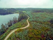 Дорога режет до конца лесистый ландшафт стоковые изображения