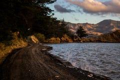 Дорога сельской местности около озера и гор стоковые фотографии rf