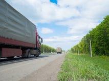 Дорога с moving автомобилями и зелеными окрестностями на сторонах Стоковые Фотографии RF