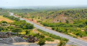 Дорога через холмы и зеленые деревья Стоковые Фото