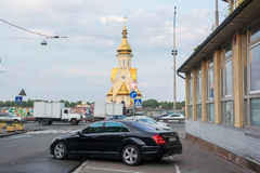 Дорогие автомобили и церковь в Podil, Украине, Kyiv редакционо 08 03 2017 Стоковая Фотография