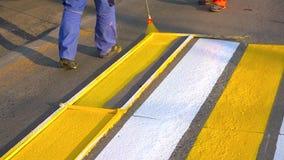 Дорожная разметка Крася линии дороги Работники рисуют белые и желтые пешеходные линии на пешеходном переходе сток-видео