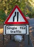 Дорожный знак движения отдельного файла показывая что узкие части дороги от левой стороны стоковая фотография