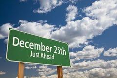 Дорожный знак зеленого цвета 25-ое декабря как раз вперед над небом Стоковое Фото