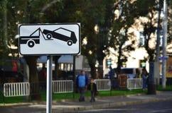 Дорожный знак который показывает эвакуатор автомобиля, который поднимает пассажирский автомобиль на борту стоковые фотографии rf