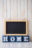 Доска и ДОМАШНИЙ знак сделанные из деревянных блоков на деревянном backgro Стоковое Изображение RF