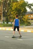 Доска конька катания мальчика на месте для стоянки лета около электростанции, вид сзади стоковые изображения rf
