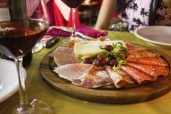 Доска мясной закуски с вином на таблице стоковые фото