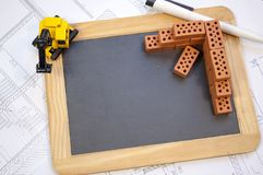 Доска на плане строительства или светокопии, небольшие кирпичи клинкера и экскаватор стоковое фото