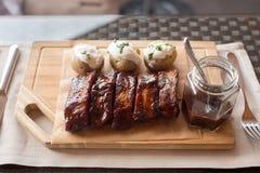 Доска нервюр и potatoe барбекю на деревянном Стоковая Фотография