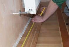 Доска обхода & Architrave ` S ремонтника вручает устанавливать дуб доски обхода деревянный пол стоковые фотографии rf