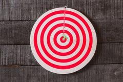 Доска дротика с стрелкой дротиков в центре цели на деревянном backgro Стоковое Изображение