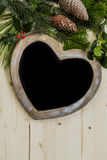 Доска сердца рождества на деревянной предпосылке с праздничной листвой Стоковые Изображения RF