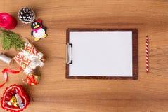 Доска сзажимом для бумаги замечает модель-макет для рождества ветви ели, подарок рождества и украшения на деревянной предпосылке Стоковое Изображение