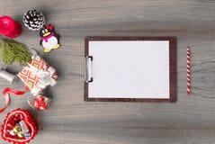 Доска сзажимом для бумаги замечает модель-макет для рождества ветви ели, подарок рождества и украшения на деревянной предпосылке Стоковое Фото