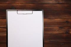 Доска сзажимом для бумаги с белым листом на деревянной предпосылке Взгляд сверху стоковые изображения rf