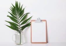 Доска сзажимом для бумаги с пустой бумагой и тропик листают в опарнике Стоковая Фотография