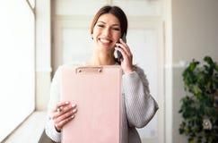 Доска сзажимом для бумаги удерживания молодой женщины говоря с телефоном на работе стоковые фотографии rf