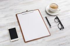 Доска сзажимом для бумаги на деревянном столе Стоковые Изображения