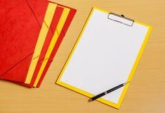 Доска сзажимом для бумаги с белыми листом, папками и ручкой на столе Стоковое Фото