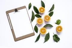 Доска сзажимом для бумаги с и апельсины стоковая фотография