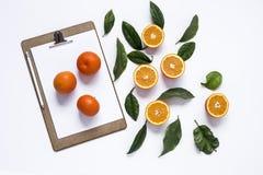 Доска сзажимом для бумаги с и апельсины стоковая фотография rf