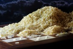 Доска с растущими кучами зерен риса, сказание о экспоненциальной функции и пределы к росту, темному небу стоковая фотография rf