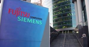Доска signage улицы с логотипом компьютеров Fujitsu Limited Сименса Современные небоскреб центра офиса и предпосылка лестниц Стоковые Изображения RF