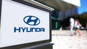 Доска signage улицы с логотипом Hyundai Мотора Компании Запачканный центр офиса и идя предпосылка людей Редакционное 4K акции видеоматериалы